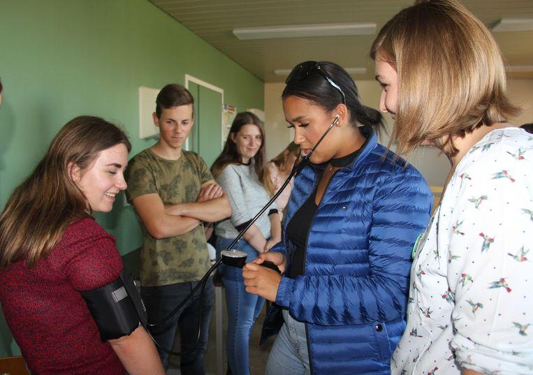 De leerlingen controleren elkaars bloeddruk tijdens de zorgberoepenrally.