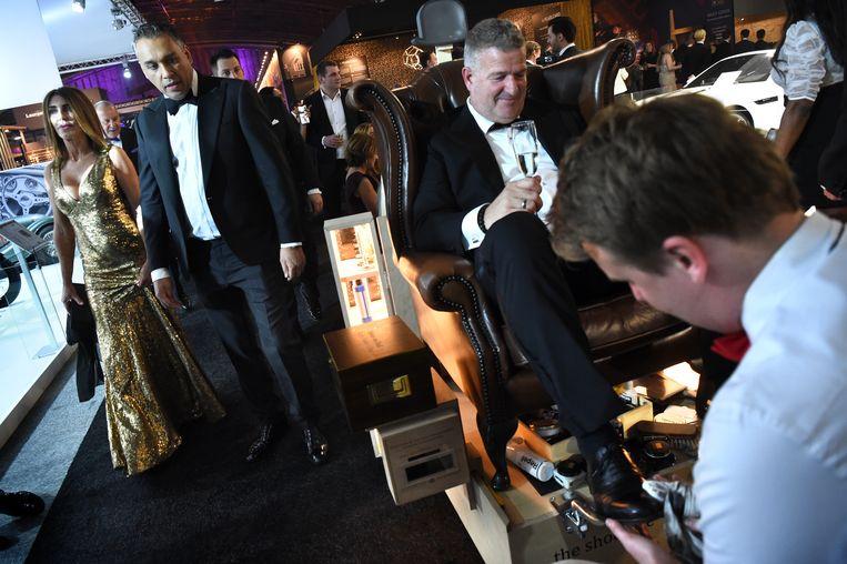 Bezoekers laten hun schoenen poetsen op de luxe-beurs Masters of LXRY in Amsterdam. Als financieel 'doorsluisland' speelt Nederland een zeer kwalijke rol in het toenemende verschil tussen arm en rijk, aldus Oxfam. Beeld Marcel van den Bergh