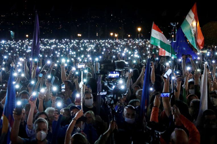 Demonstranten in Boedapest houden hun telefoons met het lampje aan omhoog uit protest tegen het ontslag van de hoofdredacteur van nieuwssite Index.  Beeld Reuters, Bernadett Szabo