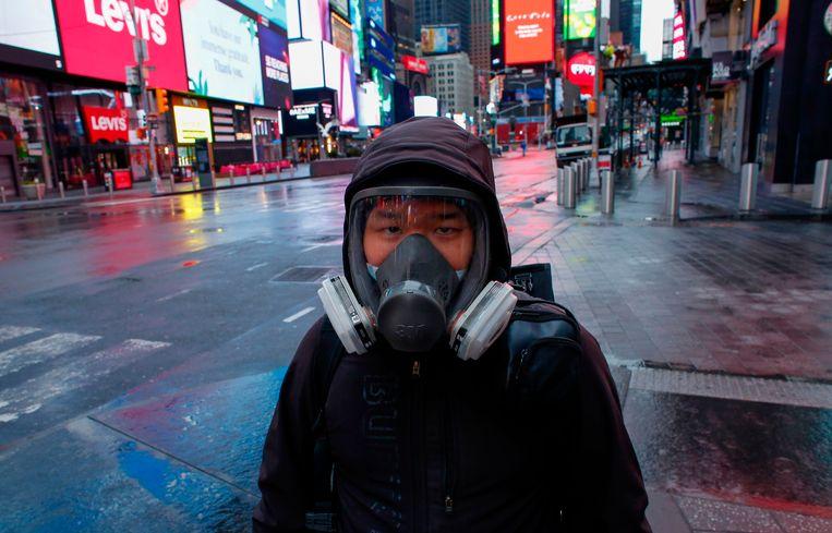 Een man met een gezichtsmasker op een verlaten Times Square. Beeld AFP