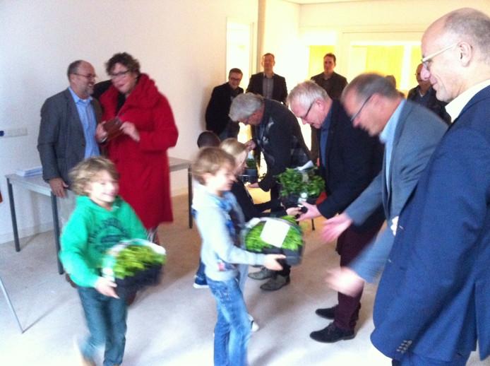 Wethouders van Landerd (rechts), Bernheze en Boekel ontvangen na de ondertekening een groen geschenk van scholieren van Bluyssen en Brink.