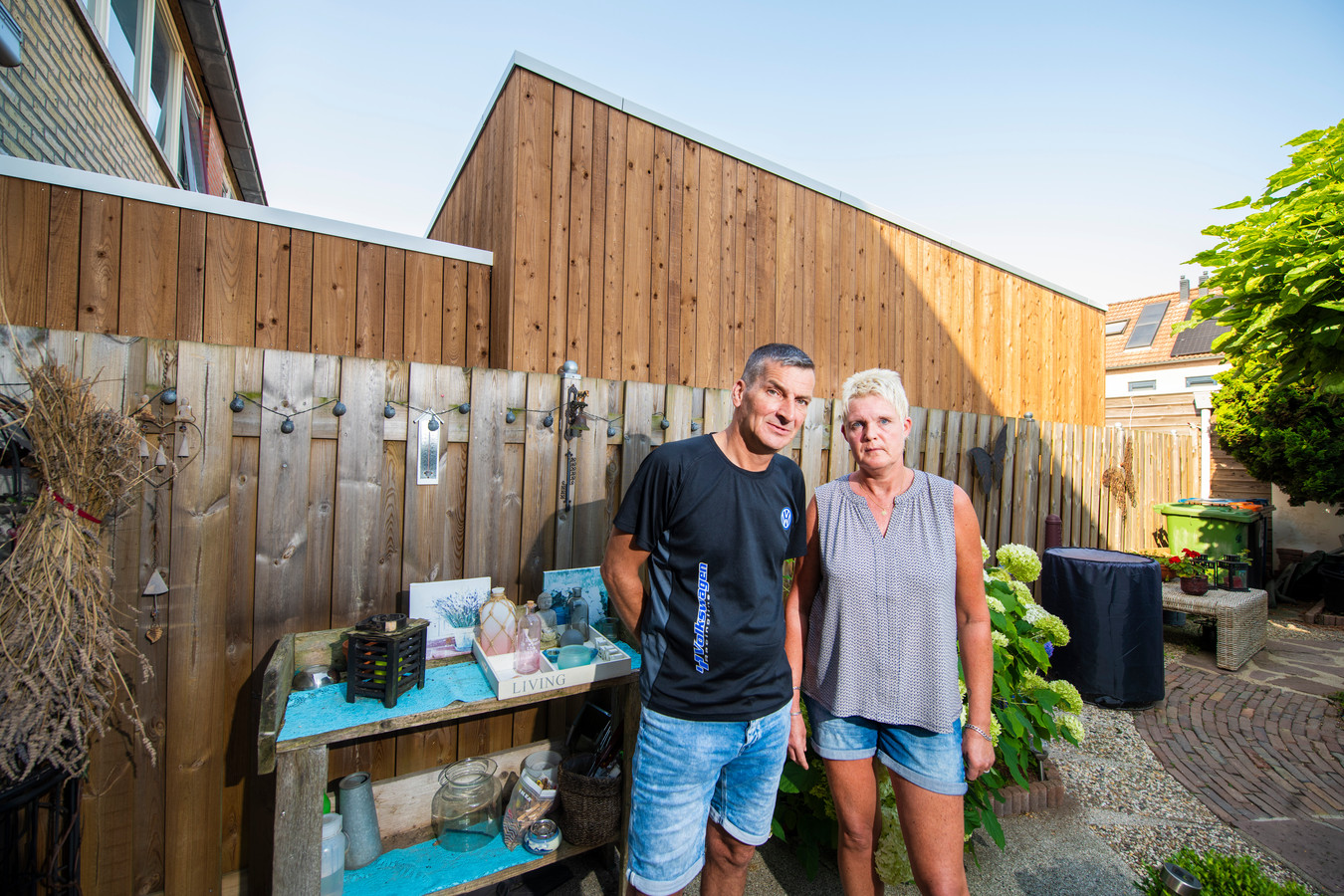 Meindert en Trudy de Haas voor de houten wand waar ze sinds vorige week tegenaan kijken.