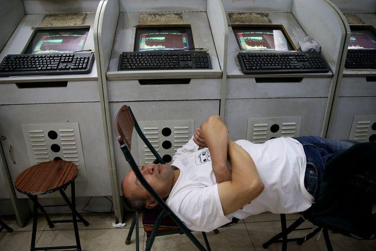 Een handelaar doet een dutje op de beurs van Peking. Beeld EPA