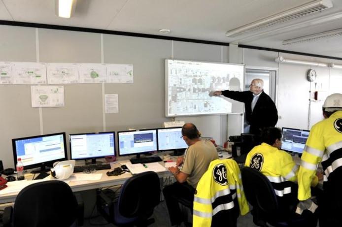 Links de nieuwe energiecentrale Moerdijk 2. Rechts de immens grote koeltoren van Moerdijk 1. ;Supervisor Gerard Akkerman legt in de controlekamer uit hoe de nieuwe energiecentrale van Essent werkt. foto's Thom van Amsterdam
