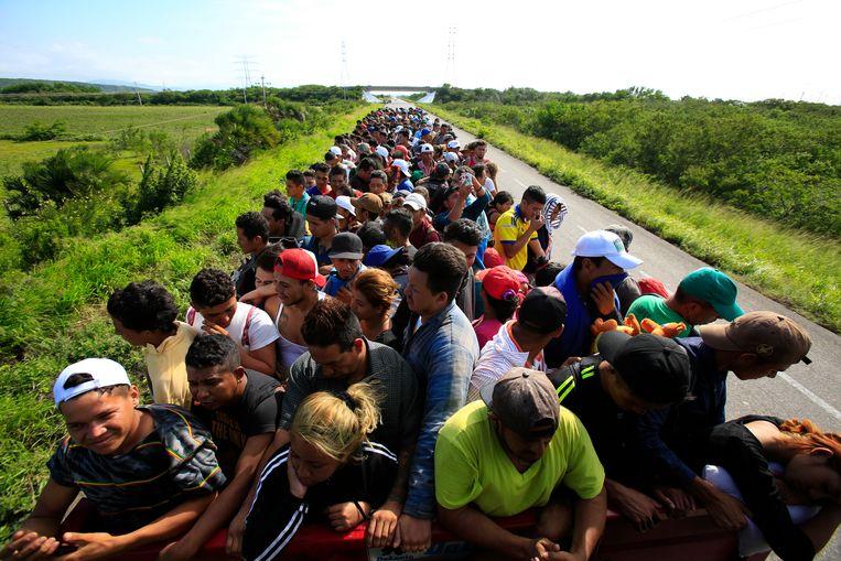 Honderden migranten liften mee op een vrachtwagen. De karavaan trekt door het zuiden van Mexico. Beeld AP