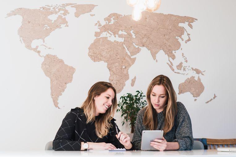 Loes en Lotte bij de wereldkaart.