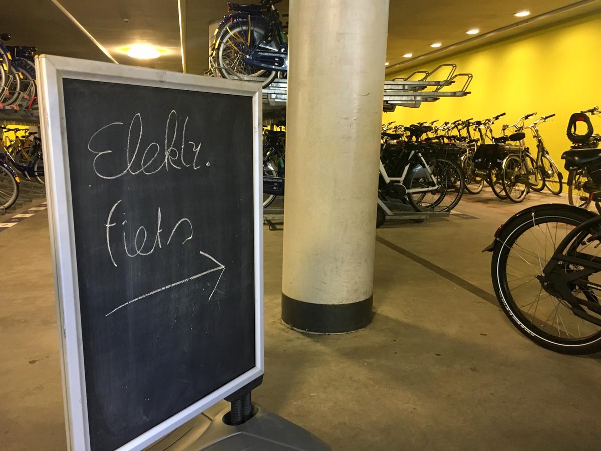 Een bord wijst bezoekers van de bewaakte fietsenstalling bij Arnhem Centraal sinds enkele dagen op het feit dat e-bikes meteen na de ingang kunnen worden geparkeerd.