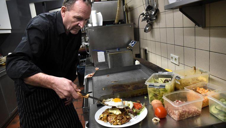 Snackbarhouder Peter Klumpkens maakt een 'gezonde' lunch met 2 hamburgers. Beeld Marcel van den Bergh