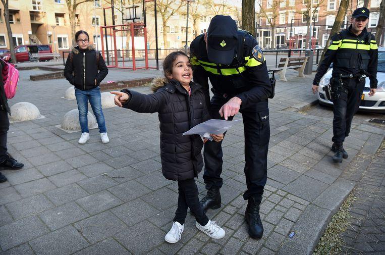 Een meisje spreekt de wijkagent in het Oude Westen in Rotterdam. Beeld Marcel van den Bergh / de Volkskrant