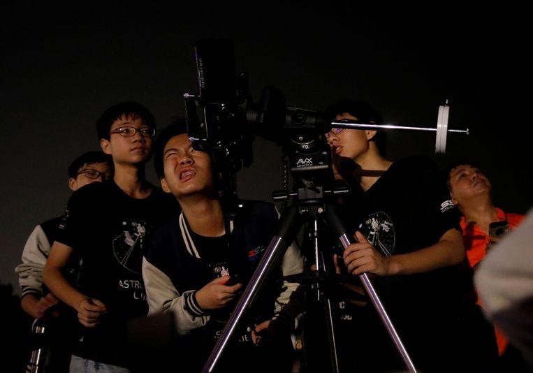 Studenten astronomie in Singapore halen hun telescoop boven om de bloedmaan te bekijken.