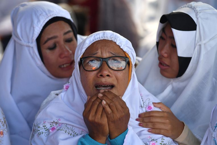 Nabestaanden bidden voor de slachtoffers tijdens de ceremonie in de haven van Tigaras.