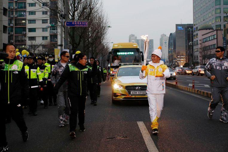 Een fakkeldrager rent - al begeleidend door de politie - door de straten van Seoul. Beeld Woohae Cho