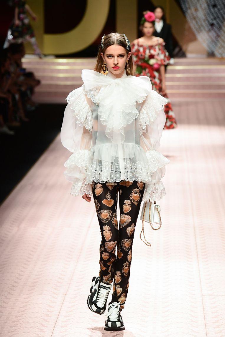 Een dramatische witte blouse met pop-artlegging en sneakers onder.