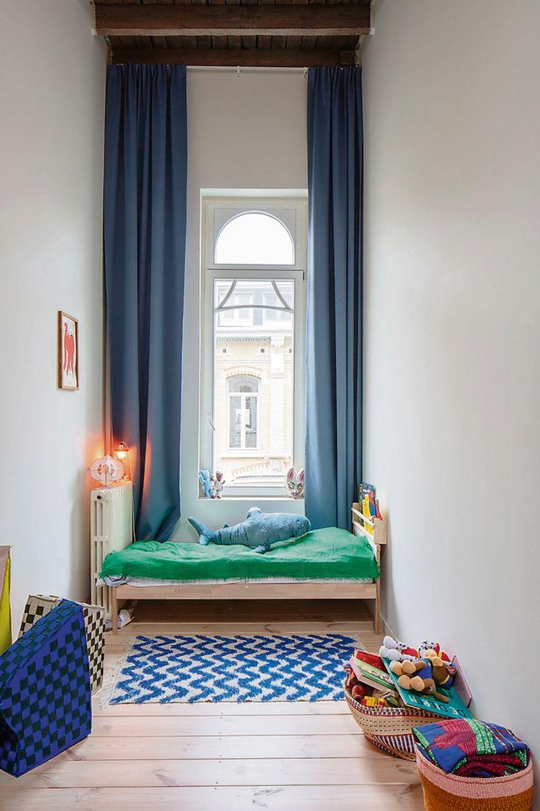Veel kleur in de slaapkamer van Omar met een vintage Deens tapijt en dekentje.
