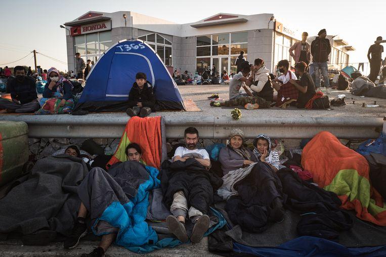 Duizenden bewoners van het afgebrande kamp Moria op Lesbos hebben hun toevlucht gezocht tot parkeerterreinen en slapen langs de kant van de weg. Beeld Zolin Nicola