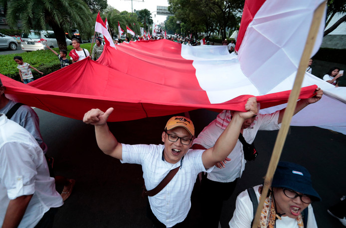 Supporters of Indonesian President Joko Widodo hold a large national Red-White flag as they celebrate during a rally in Jakarta, Indonesia, Wednesday, April 17, 2019. Widodo is on track to win a second term, preliminary election results showed Wednesday, in apparent victory for moderation over the ultra-nationalistic rhetoric of his rival Prabowo Subianto. (AP Photo/Dita Alangkara)