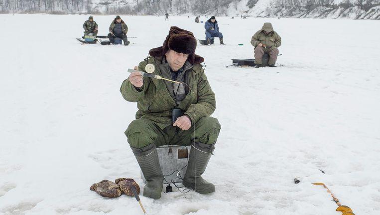 Russische mannen vissen op de bevroren Velikaja Reka. Beeld Emile Ducke