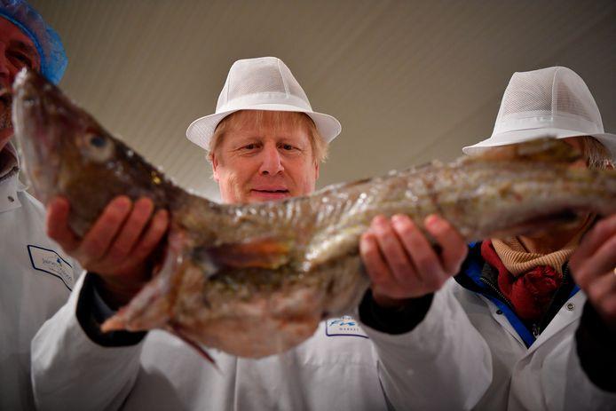 Johnson poseert met een vis op de visafslag in Grimsby, in Noordoost-Engeland.