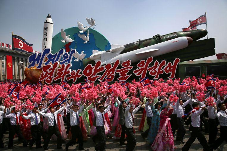 Noord-Koreanen zwaaien met de vlag van het land en plastic bloemen terwijl een vloot met raketten en het opschrift 'Voor vrede en stabiliteit in de wereld' voorbijkomt tijdens de militaire parade ter ere van de 'Dag van de Zon'.