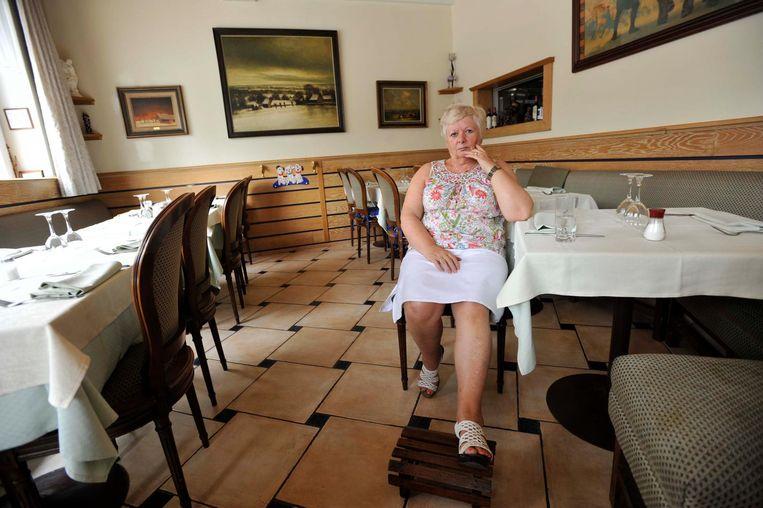 Alice Boeykens in een leeg restaurant, met haar geblesseerde been op een voetbankje.