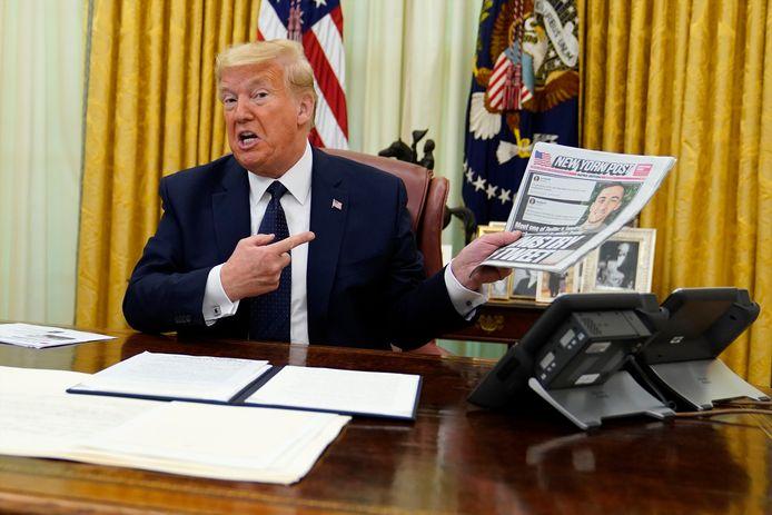 President Donald Trump houdt een exemplaar van de krant New York Post omhoog, kort voordat hij het decreet ondertekent waarin hij sociale media als Twitter en Facebook verantwoordelijk maakt voor de inhoud van berichten