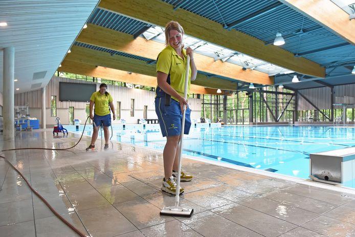 Devina van Herwijnen maakt de tegels rondom het wedstrijdbad van recreatiepark De Warande nog eens extra schoon, vlak voor de heropening dit voorjaar.