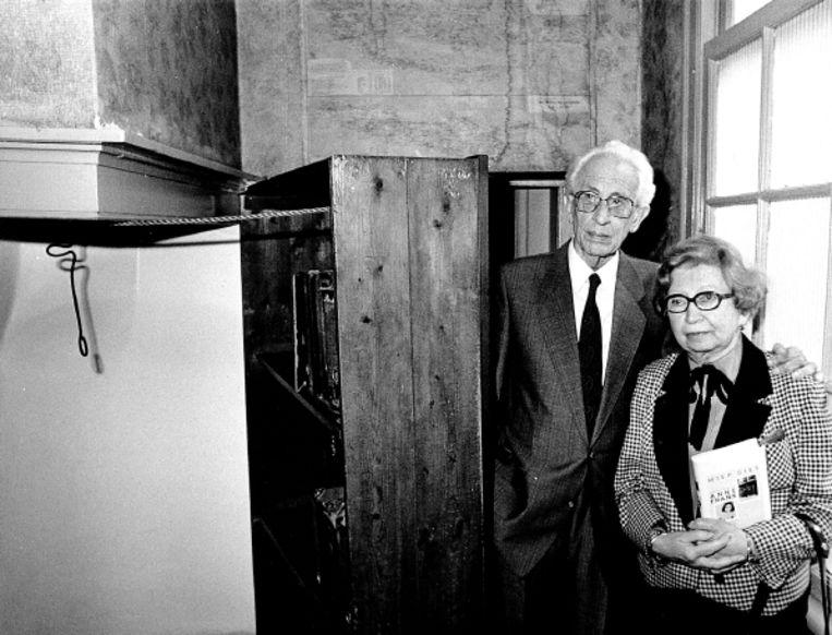 Miep en haar man Jan in het Anne Frank Huis, op 5 mei 1987. Ze staan naast de boekenkast die leidde naar de schuilplaats van de familie Frank. (FOTO EPA) Beeld EPA