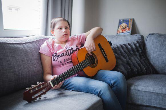 Gent, kankerpatientje Selin met haar gitaar waarop ze nummer van Stan Van Samang oefent