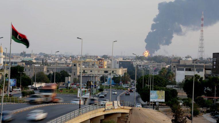 Zwarte rookpluimen bij een brandstofdepot vlakbij het vliegveld in Tripoli op 28 juli. Om de luchthaven wordt al weken hevig gevochten. Beeld epa