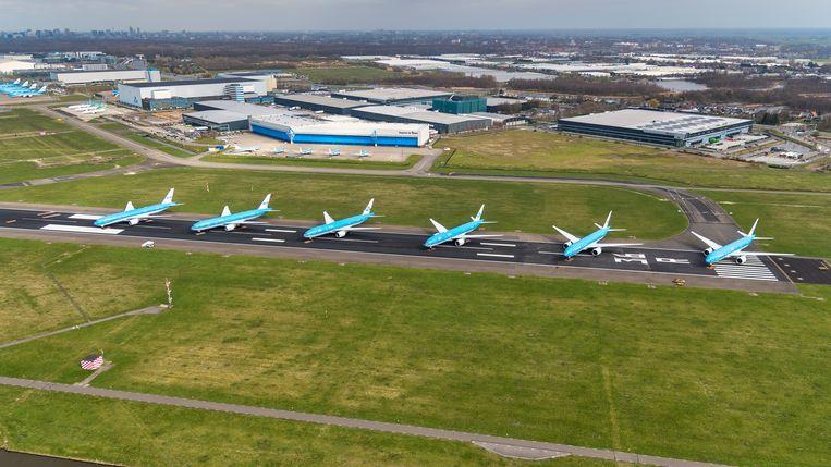 Vliegtuigen aan de grond op Schiphol. De luchthaven stelt vanwege de coronacrisis nu ook bouwwerkzaamheden uit.  Beeld ANP