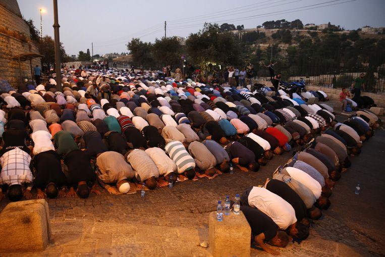 Moslims bidden zondag massaal buiten de stadspoorten van Jeruzalem uit protest tegen de veiligheidsmaatregelen. Beeld afp