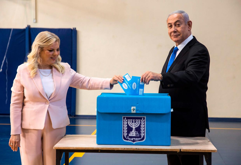 Premier Benjamin Netanyahu en zijn vrouw Sara brengen hun stem uit bij een stembus in Jeruzalem.   Beeld AFP