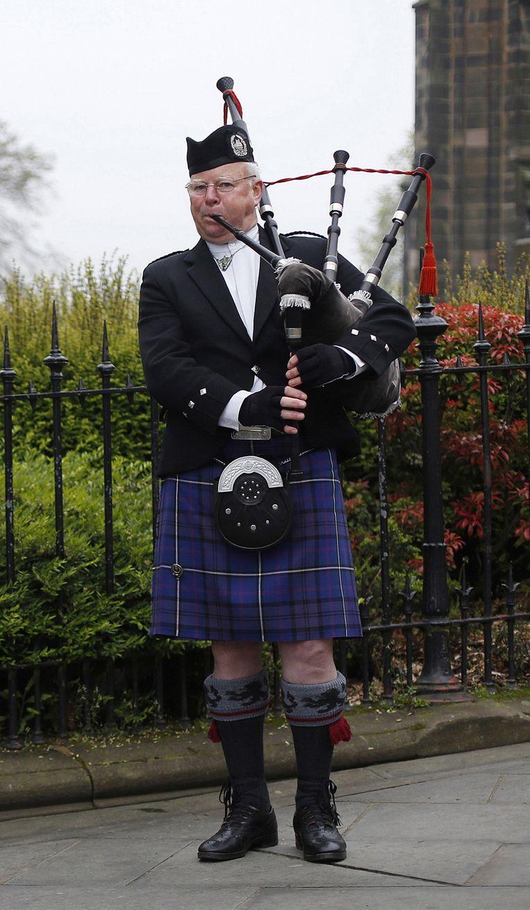 Straatmuzikant in de belangrijkste winkelstraat van de Schotse hoofdstad Edinburgh. Beeld Suzanne Plunkett / Reuters