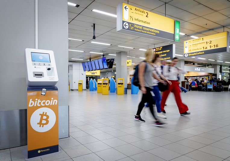 Reizigers op Schiphol die kort voor vertrek hun laatste euro's kwijt willen, kunnen deze inwisselen voor cryptomunten bitcoin en ethereum. Op de luchthaven is als proef een bitcoin-automaat neergezet. Beeld ANP