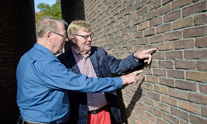 Broers Henny (links) en Harry Haverkort bij hun oude woning aan de Boeroestraat. In een zijmuur staan nog steeds de initialen die zij met hun vriendengroep in de stenen krasten.