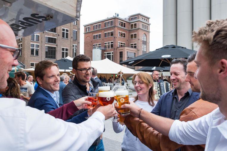 Enkele personeelsleden klinken op de 120ste verjaardag van Brouwerij Haacht met - hoe kan het ook anders - bier van eigen makelij.
