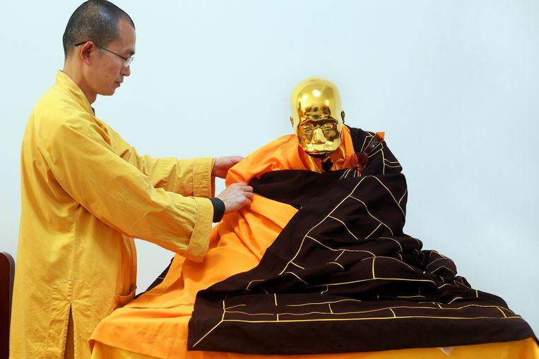 Abt Zhen Yu hult het lichaam van Fu Hou in een boeddhistisch gewaad. De monnik zal in een glazen schrijn bovenop een berg geplaatst worden.