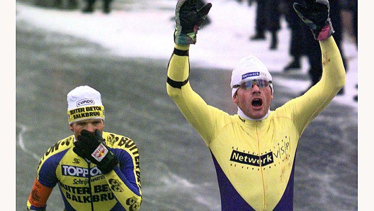 Henk Angenent gaat als winnaar over de finish van de 15de elfstedentocht. Links Erik Hulzebosch. Beeld anp