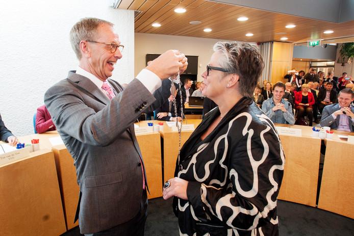 Loco-burgemeester Johan van den Brand hangt in oktober 2013 de ambtsketen om bij de kersverse nieuwe Haarense burgemeester Jeannette Zwijnenburg.