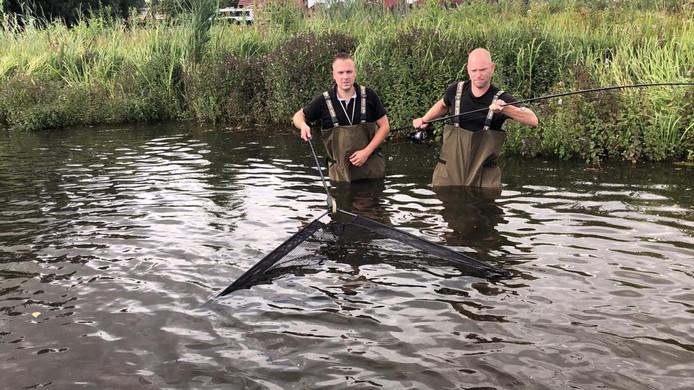 Dick Jansen (rechts) en Mark Buijl in actie op de plek waar ze in de nacht van Vrijdag op zaterdag de meerval hebben gevangen.