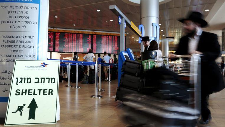 Passagiers op de luchthaven Ben Goerion in Tel Aviv lopen langs een bord dat verwijst naar schuilplaatsen. Beeld epa