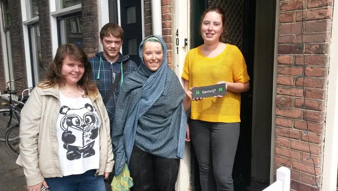 Maaike Geelhoed, Mike de Snoo en Soleï van Sloten vlnr) geven een bewoonster een bedankje voor haar gastvrijheid