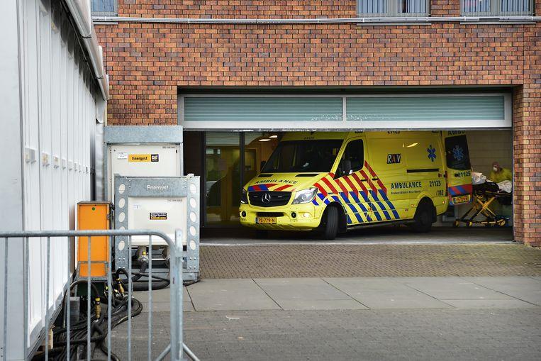 Bij ziekenhuis Bernhoven in Uden wordt een patiënt aangevoerd naar de speciaal ingerichte triagetent (links), waar zieken aan een eerste onderzoek worden onderworpen. Beeld Marcel van den Bergh / de Volkskrant