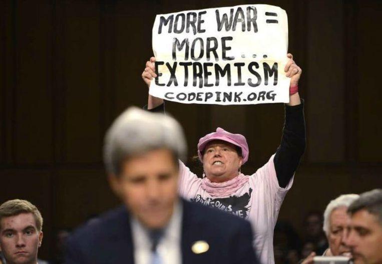 Achter de rug van de minister van buitenlandse zaken Kerry protesteert een vrouw tegen Amerikaanse aanvallen op IS. Beeld epa