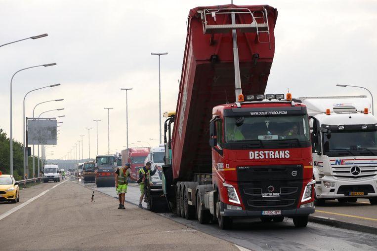 Arbeiders brengen de tweede van drie lagen asfalt aan op de E17.