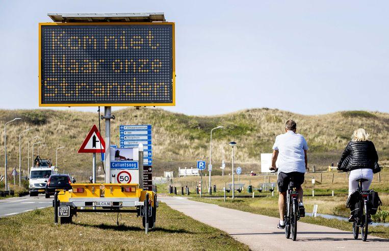 Een bord langs de weg bij de Noord-Hollandse kustplaats Callantsoog drukt bezoekers op het hart thuis te blijven.  Beeld ANP
