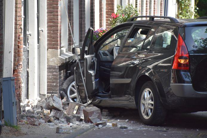 De auto ligt flink in de kreukels nadat die tegen een gevel is geklapt.