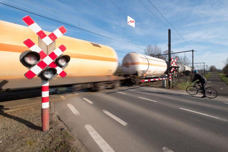 Een fietser staat voor een gesloten overweg. Volgens de burgemeester zullen de slagbomen veel vaker dicht zijn als het alternatieve goederentracé voor de IJzeren Rijn er komt.