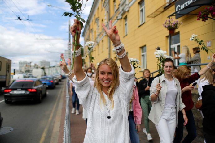 Veel vrouwen in witte kleren en met bloemen protesteren tegen politiegeweld en de verkiezingsuitslag