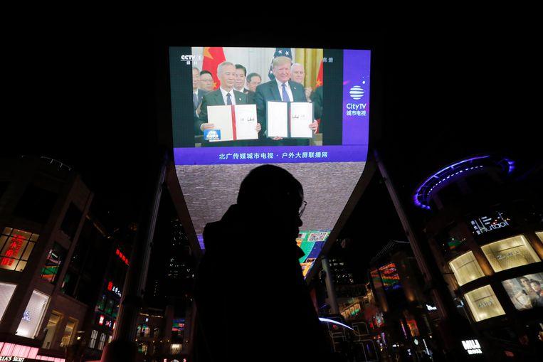 Een groot scherm aan een shoppingcenter toont hoe de leiders van de VS en China poseren na de ondertekening van het voorlopige handelsakkoord.